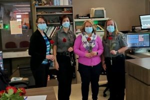 Mothers from the McHenry Police Dept stand with roses from Plaspros